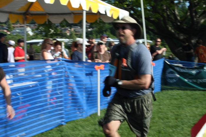 John, running to ring the bell at the finish line, after finishing the kayak leg of the race for his team